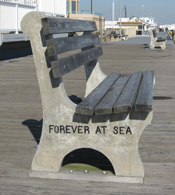 a bench on the boardwalk with an inscription - forever at sea